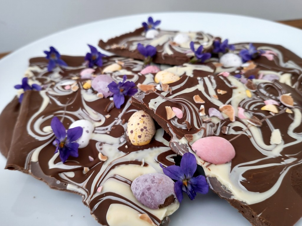 Pastel coloured mini eggs set in marble swirled chocolate bark and decorated with sweet violets